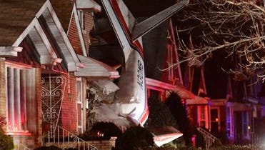 A small twin-engine cargo plane is seen after it crashed into a home on Chicago's southwest side early today shortly after taking off from Midway International Airport. A fire department spokesman says two occupants of the home were unhurt. Authorities did not immediately release information about the pilot's condition.