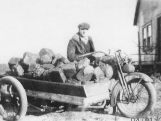 Clinton Gardner rides a motorcycle with a sidecar filled with coal. Gardner delivered coal by motorcycle during the Depression