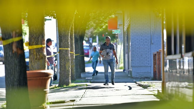 WORCESTER - Solomon Obeng, an investigator in the crime scene unit  of the Worcester Police Department, and police detectives investigate a reported stabbing Sunday in Main South. The crime scene extended from 802 Main St. to the entrance to Oread Castle Park.