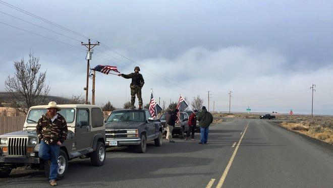 People wave American flags near the Malheur National Wildlife Refuge, Thursday, Feb. 11, 2016, near Burns, Ore.