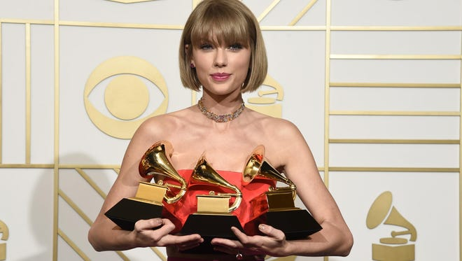 """Taylor Swift poses in the press room with the awards for album of the year for 1989, pop vocal album for 1989 and best music video for """"Bad Blood"""" at the 58th annual Grammy Awards at the Staples Center on Monday, Feb. 15, 2016, in Los Angeles."""