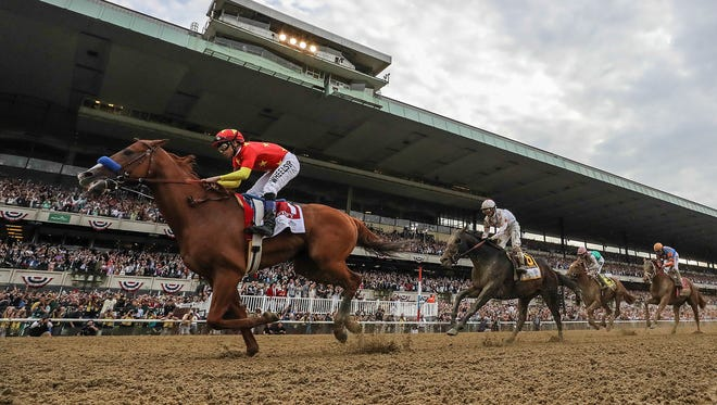 Justify with jockey Mike Smith wins the Belmont Stakes and the Triple Crown of horse racing. 