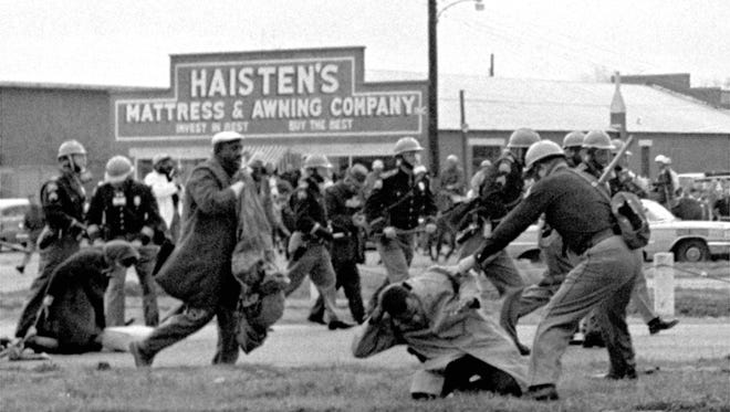 """FILE - In this March 7, 1965 file photo, state troopers use clubs against participants of a civil rights voting march in Selma, Ala. At foreground right, John Lewis, chairman of the Student Nonviolent Coordinating Committee, is beaten by a state trooper. The day, which became known as """"Bloody Sunday,"""" is widely credited for galvanizing the nation's leaders and ultimately yielded passage of the Voting Rights Act of 1965. (AP Photo/File)"""