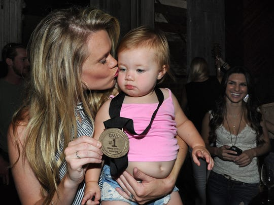 Nicolle Galyon kisses her baby and displays her CMA No. 1 song medallion Aug. 25, 2014, in Nashville.
