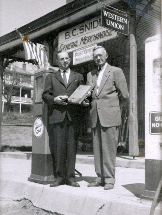 Bruce C. Snider, right, receives an award for service from a Gulf Oil representative, sometime during the 1950s at Snider's Store in Williamson.