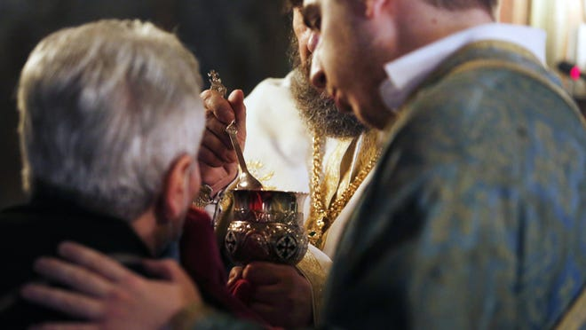 In this Sunday, May 24, 2020 photo, a Greek Orthodox priest gives to a faithful the Holy Communion during the Sunday mass at a church, in the northern city of Thessaloniki, Greece. The church and its followers insist it is impossible for any disease to be transmitted through Holy Communion _ including the new coronavirus, which scientists say can spread through respiratory droplets when an infected person coughs, sneezes or speaks, or by a person contaminating their hands and then touching their face.