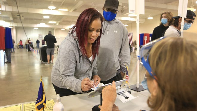 Jamila Evans signs the screen as she and her husband, James Evans, back, prepare to vote for the first time at the Meadowlark Building at the Kansas State Fair fairgrounds Tuesday.