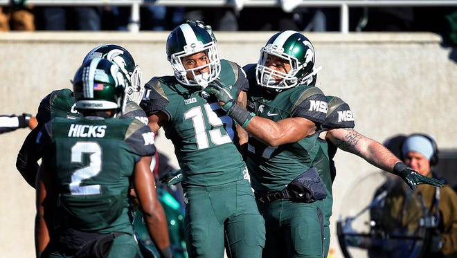 Nov 14, 2015: Michigan State Spartans cornerback Tyson Smith (15) and Michigan State Spartans cornerback Darian Hicks (2) celebrate defense stop during the 1st quarter of a game against the Maryland Terrapins at Spartan Stadium.