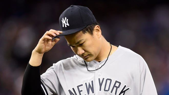 New York Yankees' Masahiro Tanaka walks off the field after the sixth inning of a baseball game against the Toronto Blue Jays on Wednesday, June 1, 2016, in Toronto.