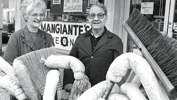 Margaret and Eugene Mangiante stand behind the broom