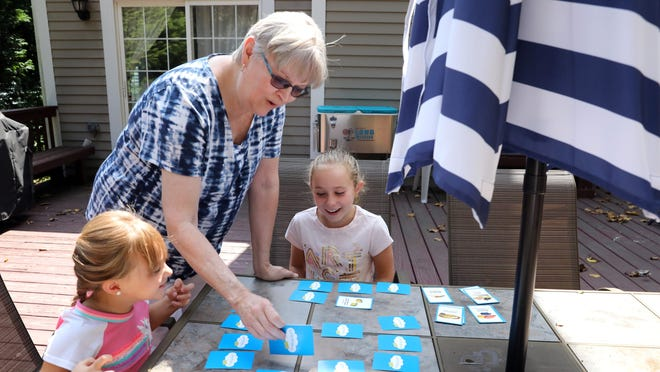 Yonkers elementary school teacher Irene Bordes, 66, made the decision to retire early because of her concerns with COVID and to help her son and daughter-in-law with child care for her three grandchildren. Bordes plays a memory card game with her granddaughters Sammie, 5, and Charlotte, 8, at her family's home in Yorktown Heights.