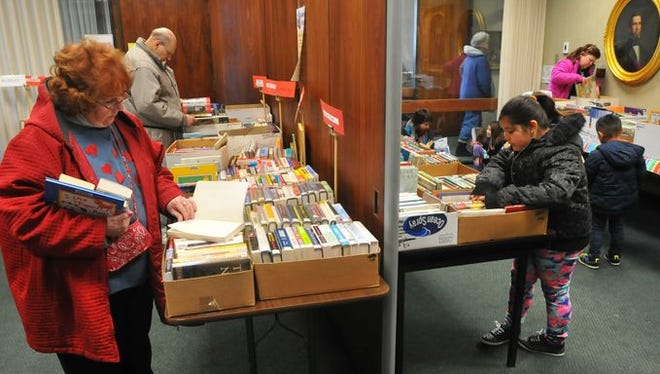 Shoppers select books in one corner of the Bard Room at Morrisson-Reeves Library during the February book sale. Another book sale opens Wednesday to the public.