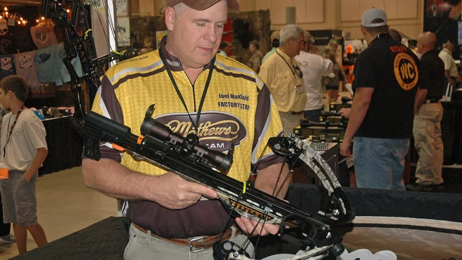 Joel Maxfield of Mathews Inc., shows off one of the crossbows that was on display at the Buckmasters Expo in the Renaissance Montgomery Hotel & Spa at the Convention Center recently.