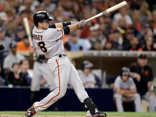 San Francisco Giants' Buster Posey hits a two-RBI double during the fifth inning of a baseball game against the San Diego Padres Friday, Sept. 23, 2016, in San Diego. (AP Photo/Gregory Bull)