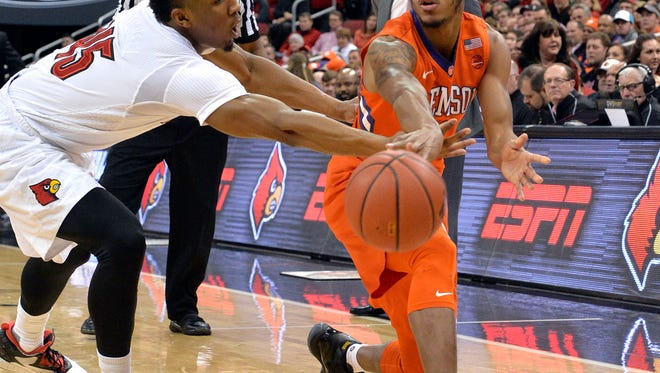 Louisville's Donovan Mitchell (45) attempts to block the pass of Clemson's Marcquise Reed (2) during the first half of an NCAA college basketball game, Thursday, Jan. 19, 2017, in Louisville, Ky. (AP Photo/Timothy D. Easley)