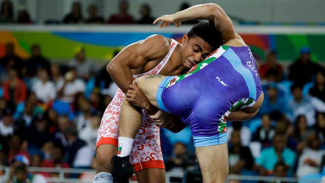 Puerto Rico's Franklin Gomez competes against Bulgaria's Borislav Stefanov Novachkov, blue, during the men's 65-kg freestyle wrestling competition at the 2016 Summer Olympics in Rio de Janeiro, Brazil, Sunday, Aug. 21, 2016.