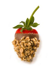 Chocolate-covered strawberry coated with peanuts at