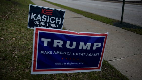 Campaign signs for John Kasich and Donald Trump are