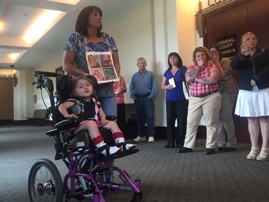 Vickie Hess stands with Maddie Belt, 1, who was severely