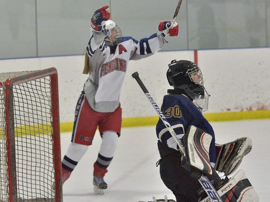 Thrusting her arms into the air after scoring is PCS Penguins junior defenseman Brianna Waggoner. The dejected goalie for Grosse Pointe South is Isabella Strickler.