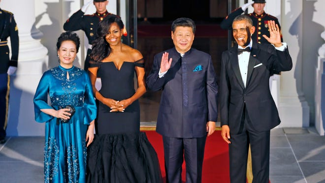 That's a cheerful group! President Barack Obama, Chinese President Xi Jinping,  wave next to wives Peng Liyuan and Michelle Obama.