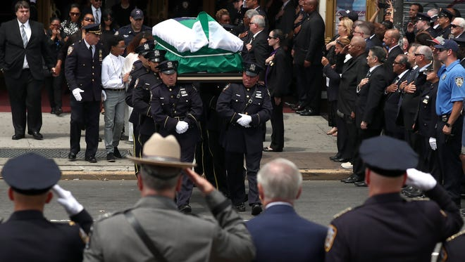 The casket of slain NYPD Officer Miosotis Familia is carried from the World Changers Church after funeral services in the Bronx. The 48-year-old mother of three was shot by an ex-convict July 5 while sitting in a police vehicle.