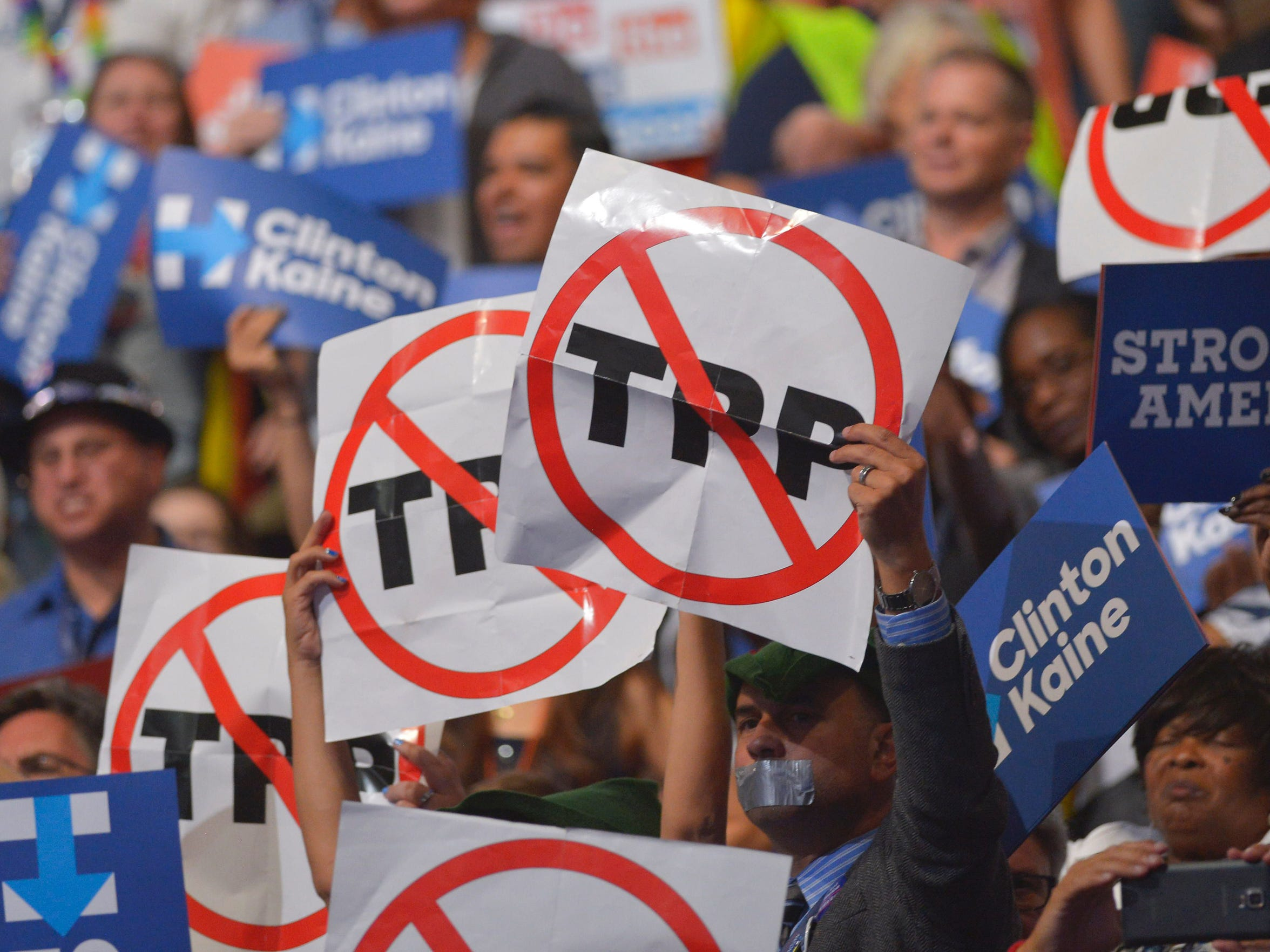 People hold signs against the Trans Pacific Partnership on Day 3 of the Democratic National Convention at the Wells Fargo Center, July 27, 2016, in Philadelphia, Penn.