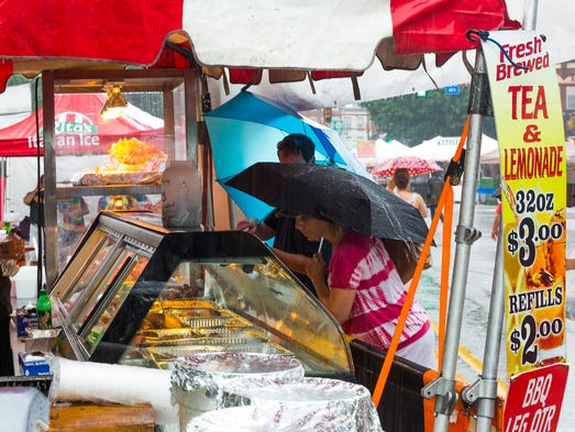Festival attendees buy food as storms move in on Saturday