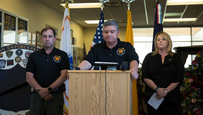 Doña Ana County Sheriff Enrique Vigil, center, looks down before speaking at a press conference, August 13, 2016, involving the death of Hatch Police Officer Jose Chavez. With him is Doña Ana County Undersheriff Ken Roberts, left, and Public Information Officer for DASO Kelly Jameson.