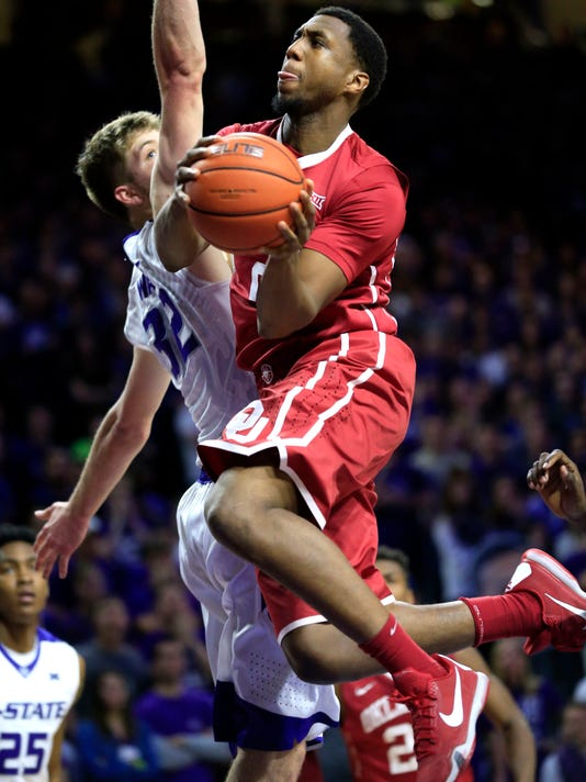 Oklahoma forward Dante Buford (21) shoots while covered by Kansas State forward Dean Wade (32) during the first half of an NCAA college basketball game at Bramlage Coliseum in Manhattan, Kan., Saturday, Feb. 6, 2016. (AP Photo/Orlin Wagner)