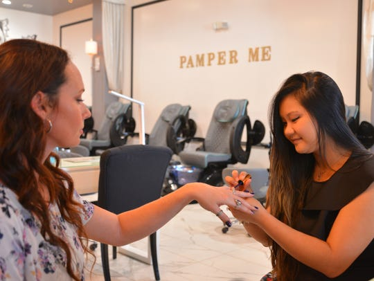 Thao Tran touches up Victoria Bellucci-Kellam's nails.