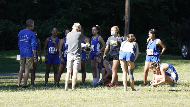 Adrian cross country head coach Tom MacNaughton talks with his team prior to Friday's race at Heritage Park.