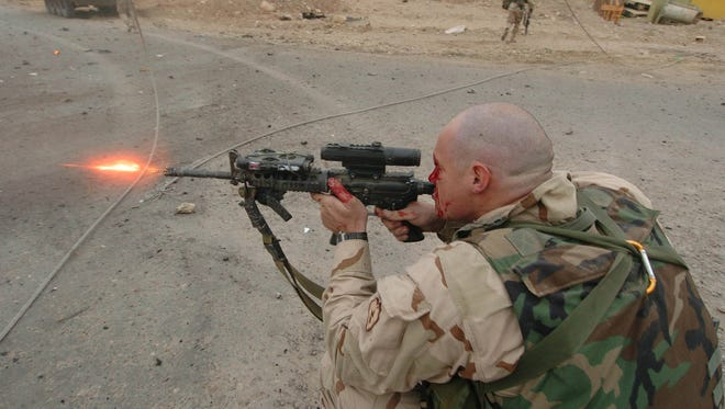 Although wounded, Staff Sgt. Shannon Kay, of 1st Battalion, 24th Infantry Regiment, fires on an enemy position after being attacked with a car bomb, Dec. 11, 2004, in Mosul, Iraq. The debate about striking Syria is also revealing a strain of isolationism growing inside a battle-weary military that has spent more than a decade supporting high-tempo war operations overseas.