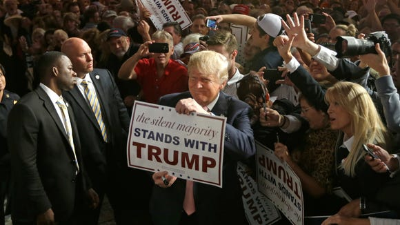 Donald Trump shows off a sign during a campaign stop