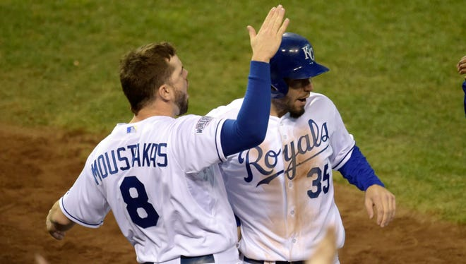 Royals first baseman Eric Hosmer celebrates with third baseman Mike Moustakas after scoring a run in Game 6.