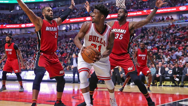 Chicago Bulls forward Jimmy Butler (center) is defended by Miami Heat guard Wayne Ellington (left) and forward Willie Reed (right) during the second quarter at the United Center.