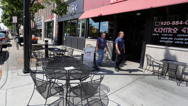 Pedestrians walk past tables and chairs on the sidewalk outside Kentro Gyro's on Washington Street August 17, 2016.