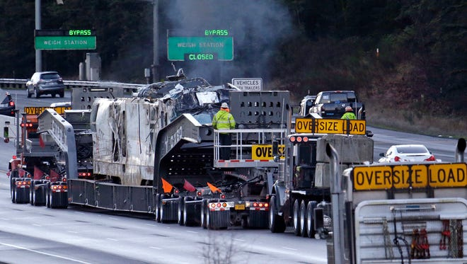 The engine from an Amtrak train that crashed  onto Interstate 5  on Monday, is transported away from the scene, Wednesday, Dec. 20, 2017, in DuPont, Wash.