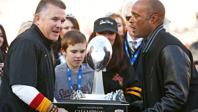 ASU coach Todd Graham and athletic director Ray Anderson lift the Sun Bowl trophy in 2014.