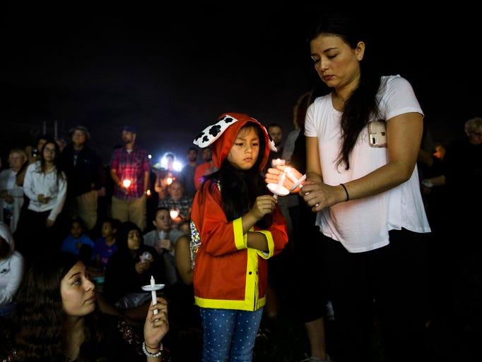 Cinthia Rios helps Jasmine Battifora, 6, light her
