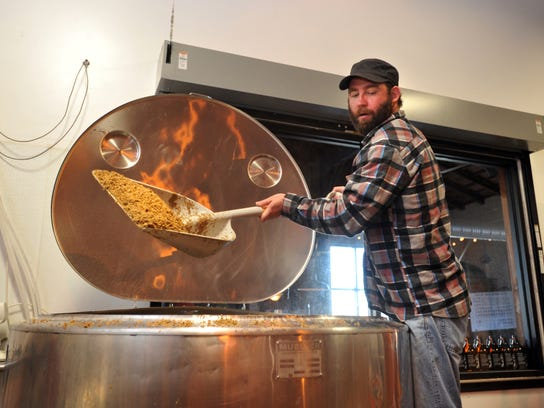 In this file photo, Burley Oak Brewing Co. owner Bryan Brushmiller shovels grain out of the mash tun.