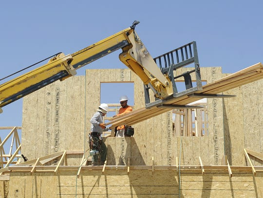 Laborers work on a house under construction in Fernley.