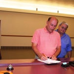 Yerington Mayor George Dini last Thursday signs the recording documents at the Lyon County Recorder's Office after the BLM officially issued the patents to transfer the 10,058 acres of BLM property to the City of Yerington. Pictured with him are (from left) Tim Arnold, Nevada Copper vice president of operations; Dini; Greg French, Nevada Copper vice president, senior project manager; and Yerington City Manager Dan Newell.
