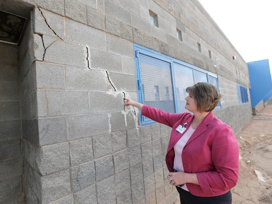 Valley View Middle School Principal Penny Bankston shows a large crack running down the side of her school. The crack is one of many which are visible from inside classrooms.