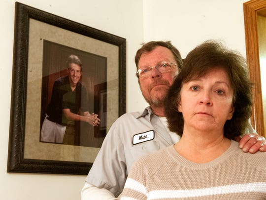 Matt and Connie Garber with a picture of Brian behind them in their home.