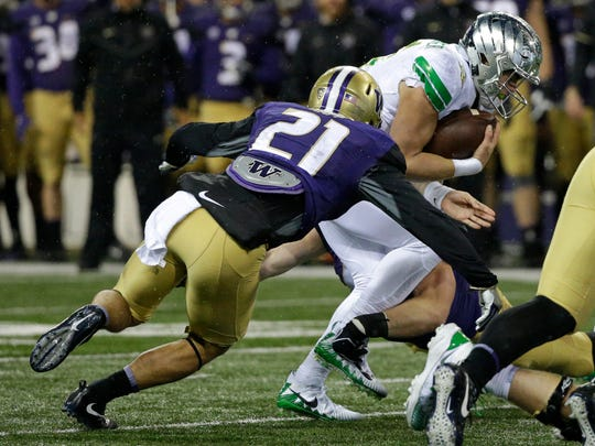 Oregon quarterback Braxton Burmeister, right, is tackled by Washington's Taylor Rapp (21) in the first half of an NCAA college football game, Saturday, Nov. 4, 2017, in Seattle. (AP Photo/Ted S. Warren)