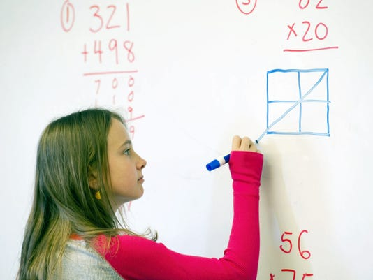 Evelynn Renner takes over at the whiteboard to describe to the class how she solved a problem during Marcus Billings' math class at Orendorf Elementary School. Billings said third-graders now do more multi-step word problems in math class.