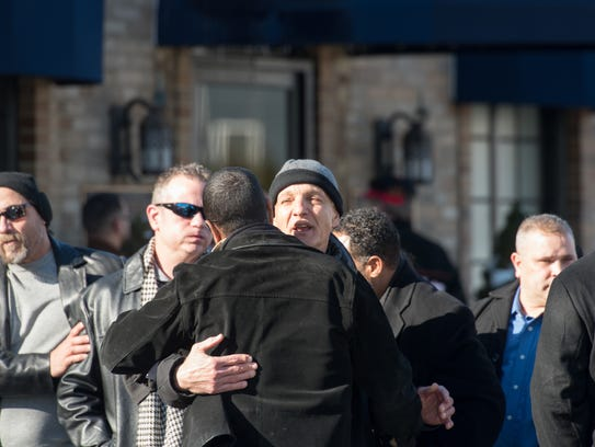 People embrace outside the funeral home. Visitation