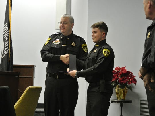 Chemung County Undersheriff William Schrom  hands Cody Marvin his graduation certificate at the Basic Training and Peace Officer Academy graduation ceremony Friday, Dec. 15, 2017.