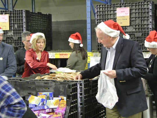 Officials and community leaders pack bags for the Food
